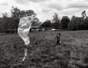 A black and white photo taken in a field. There is an elongated giant bubble on the left hand side of the image looking as if it is about to attack a young boy on the right hand side of the image. The boy was in mid run, his body twisted as he was changing direction.