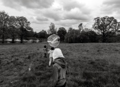 A black and white photo of the back of three boys. Two of them who were further away from the camera were chasing a giant round bubble. The oldest boy was closest to the camera. He stood calmly wearing a hoody on his head watch the commotion.
