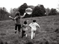 An image of the backs of three boys. They were running away from the camera chasing a large bubble. The eldest was jumping in the air trying to catch it.
