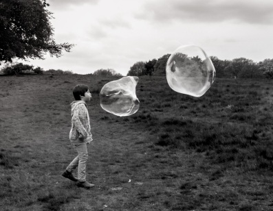 A black and white photo of a boy standing on the left hand side of the image. Two giant bubbles were that was larger than his head were floating towards him from the right hand side. He was blowing the closest bubble that was a few inches from his face.